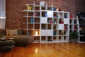 Une bibliothèque toute en cubes, anime un mur de briques.