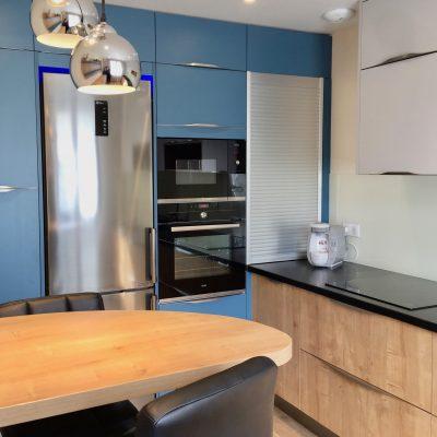 Cuisine lumineuse et optimisée, plan de travail en stratifié bois, assorti aux portes, granit noir, carrelage  bois, portes  colorées  bleu et gris clair