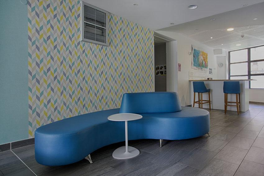 Plan bar, fresque murale, canapé haricot bleu, pouf haricot blanc, table métal sur pied, papier peint graphique, sol carrelage gris