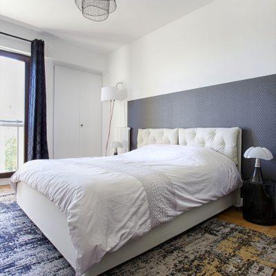 Une chambre parentale noir et blanc, lit 2 personnes, tv encadrée par 2 lés de papier peint, tête de lit papier peint, lit coffre molletonné,