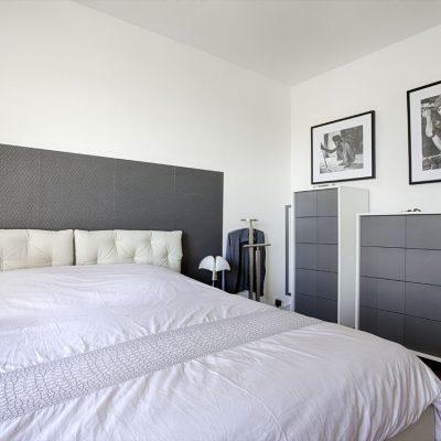 Une chambre parentale noir et blanc, lit 2 personnes, tv encadrée par 2 lés de papier peint, tête de lit papier peint, lit coffre molletonné, et deux commodes grises et blanches