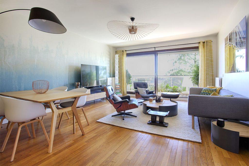 lampe arc noire, table chêne, fauteuils table blancs, parquet chêne style scandinave , meuble tv, rideaux jaune oeillets, vertigo