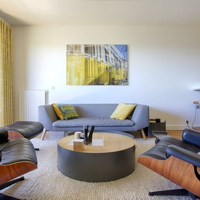 Séjour lumineux avec mobilier contemporain, tables basses rondes pour faciliter la circulation, tableau plexiglas sérigraphie, et fauteuils eames, tapis moelleux en laine tissée