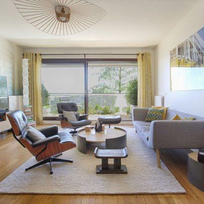 Dans le séjour, une belle lampe Arc, et une grande table chêne, avec ses quatre fauteuils de table blancs. Papier peint fresque