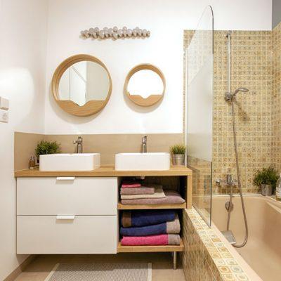 Une salle de bain d'époque dont le carrelage a été partiellement conservé, réveillé par un mur bleu sourd, des miroirs chêne ronds, avec leur petit rangement. Le meuble de salle de bain ikea a été amélioré pour faciliter l'accès à la trappe technique de la baignoire.