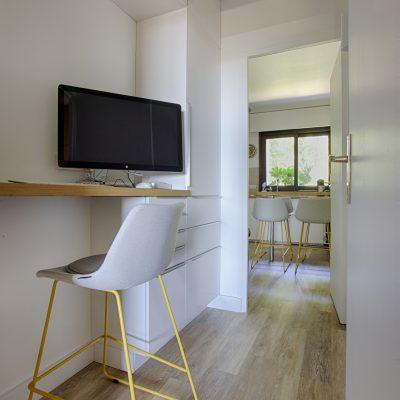 Un coin bureau  installé dans le couloir menant à la cuisine, les meubles servent à la fois de rangement cuisine ou bureau .  Un voile chaise composée sur mesure  avec le fournisseur de l'agence.