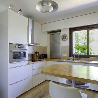 Une cuisine Ikea, plan chêne, chaise hauteur comptoir, de belles photographies personnelles aux murs.