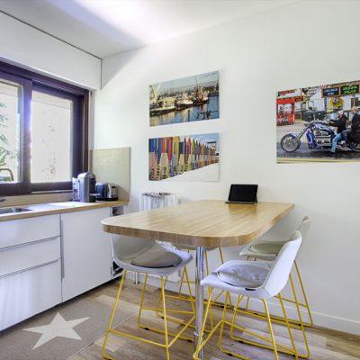 Une cuisine blanche, plan chêne, chaise hauteur comptoir, de belles photographies personnelles aux murs.