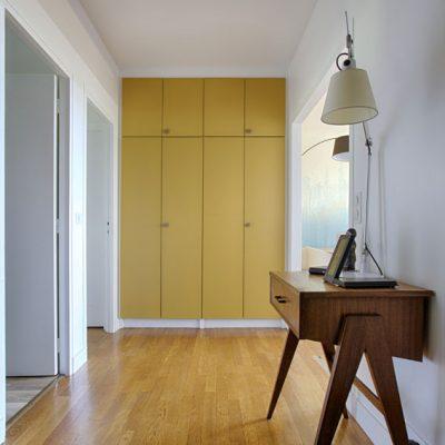 Un entrée spacieuse, , où le mur de placard répond au jaune moutarde des rideaux. Parquet poncé et vitrifié.