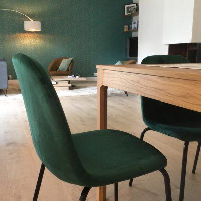 Des chaises confortables et chic, assise velours émeraude, pour un accord parfait avec le mur du fond