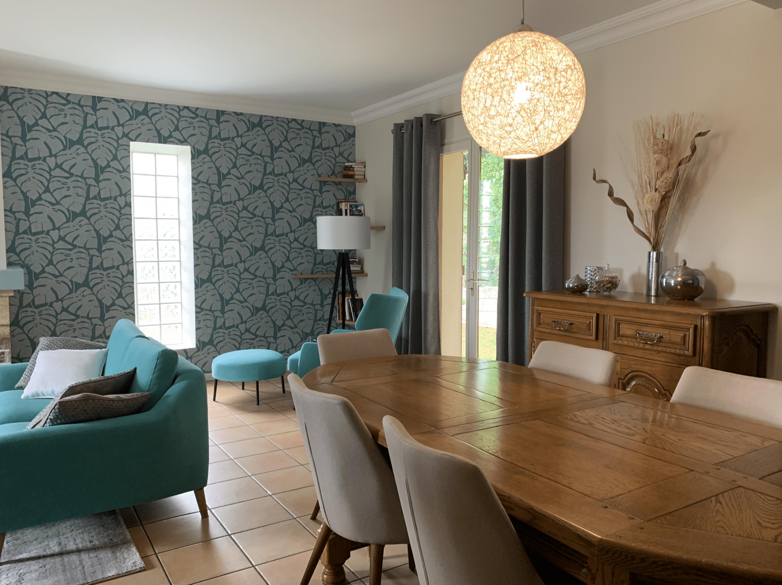 suspension boule, mobilier merisier et déco contemporaine, papier peint tropical, turquoise, canapé bleu, tapis Zuiver, chaises, table massive,